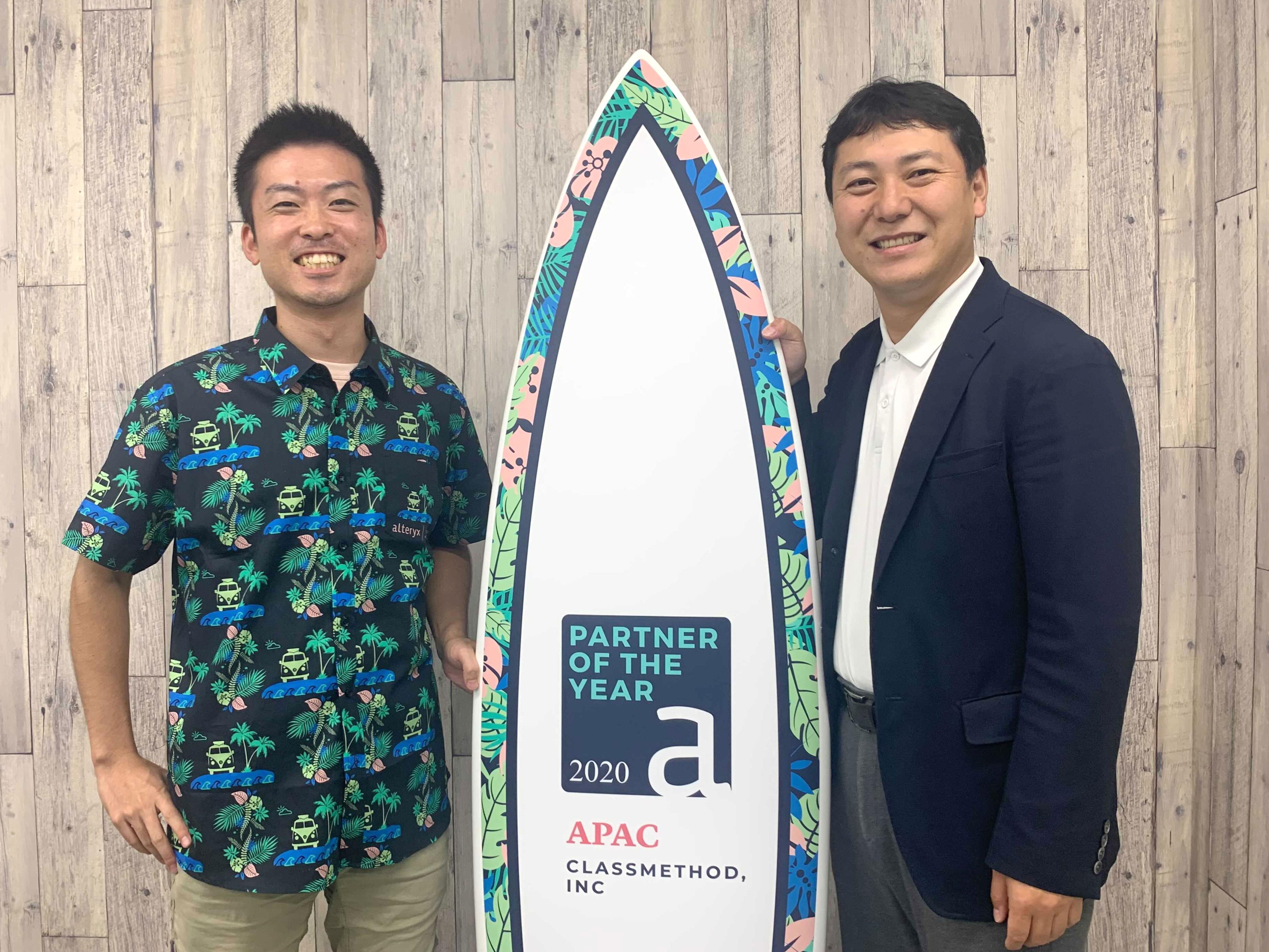 受賞記念サーフボードと、当社代表の横田聡(写真右)、データアナリティクス事業本部マネージャーの大場裕喜(写真左)